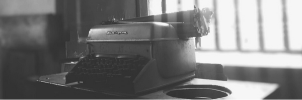 [image]: black and white image of a typewriter on a desk with a window in the background